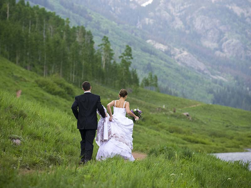 A photo of a bride and groom strolling away together