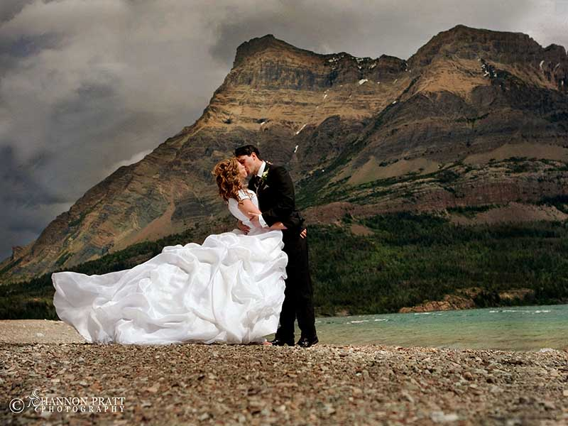 A beautiful phot of a couple enjoying a kiss as newly weds by Shannon Pratt